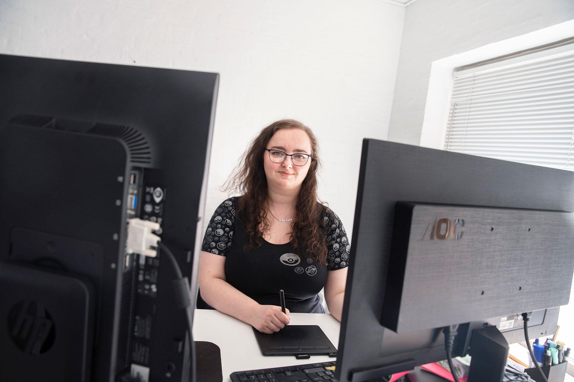 Janni Altmann siddende bag 2 computerskærme